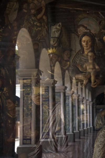 Columns reflected in the window with religious artwork | Santo Domingo church and monastery | Peru