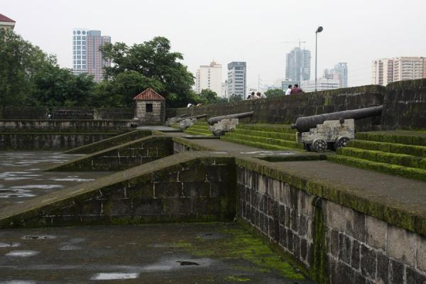 Modern Manila skyline seen from inside the old city wall | Intramuros | Philippines