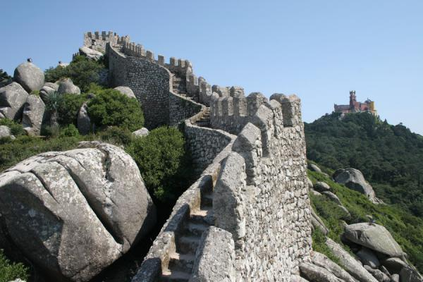 Defensive wall of the Moorish Castle with the Palace of Pena in the background | Moorish Castle | Portugal