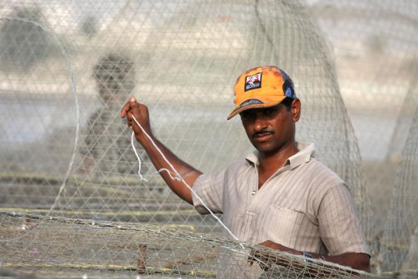 Picture of Fisherman in Al Khor repairing his net