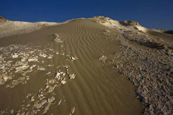 Foto di Sand blown across one of the limestone hills in the landscape of Bir ZekreetPaesaggio di Bir Zekreet - Qatar