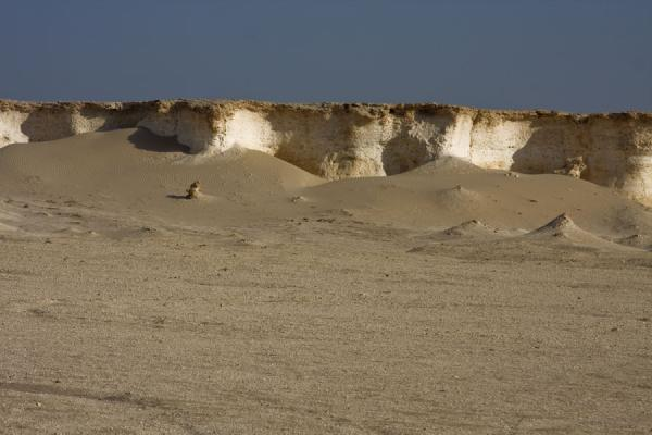 Sand dunes in front of white limestone cliffs in the landscape of Bir Zekreet | Bir Zekreet landscape | Qatar