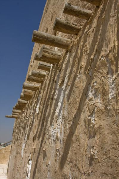 Picture of Umm Salal Mohammed fort (Qatar): Old wooden beams casting a shadow on the adobe wall of the East tower