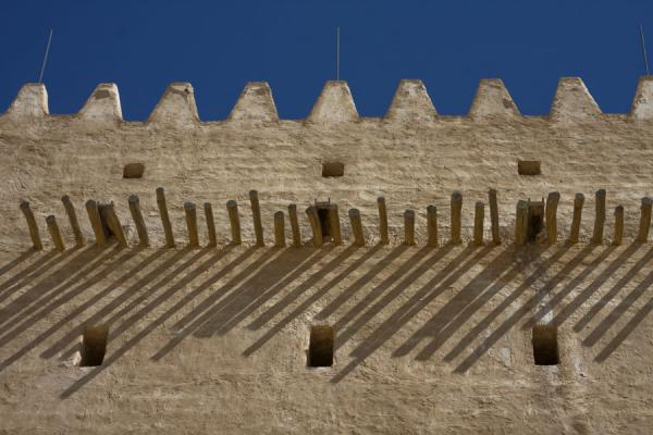 Picture of Umm Salal Mohammed fort (Qatar): Crenelated East tower with beams casting a shadow over the wall
