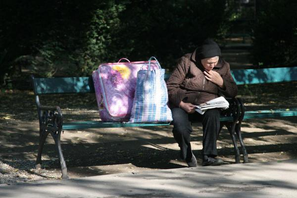 Picture of Cismigiu Gardens (Romania): Reading a paper on a bench in Cismigiu Gardens: old Romanian woman