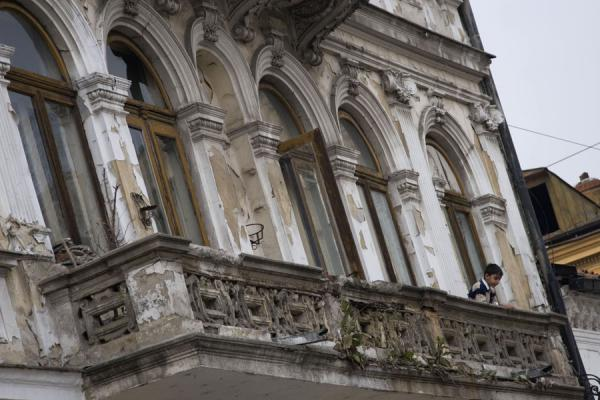 Boy looking down from the balcony of his house | Lipscani historic quarter | Romania