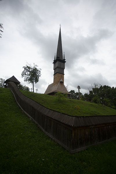 Foto van The wooden church of Șurdești is surrounded by a wooden fenceMaramureș - Roemenië