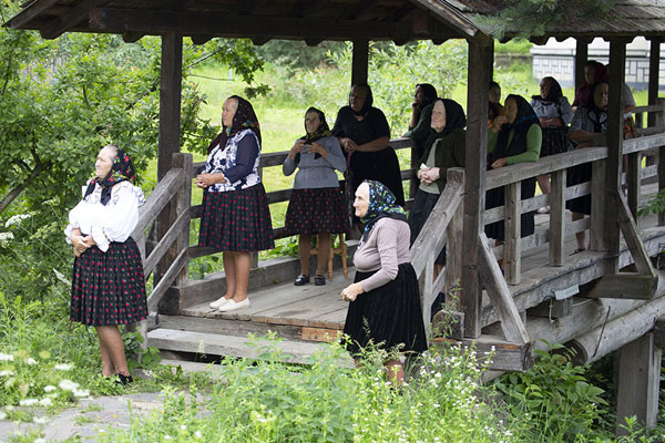 Foto van Women attending mass in traditional clothes on a wooden bridge in Poienile IzeiMaramureș - Roemenië