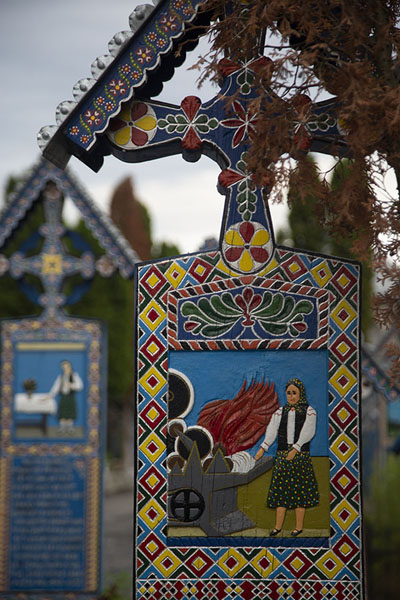 Close-up of a cross for a woman with other crosses in the background | Merry Cemetery | Romania