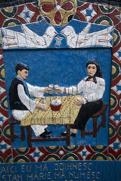 Couple having a drink, depicted on a cross at the cemetery | Merry Cemetery | Romania