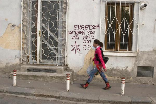 Girl walking past a slogan on a wall | Romanian people | Romania