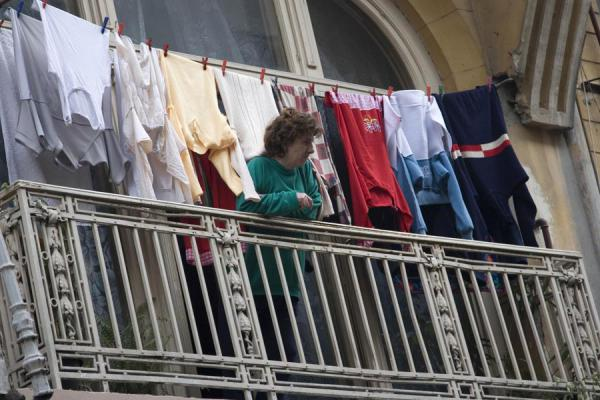 Picture of Romanian people (Romania): Woman looking down into the street from her laundry balcony