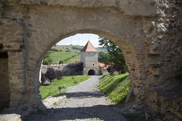 Gate with view of a tower behind it | Alcázar de Rupea | Rumania