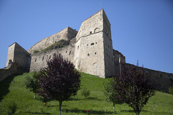 Sturdy walls of the inner citadel rising above the green hills | Rupea citadel | Roemenië