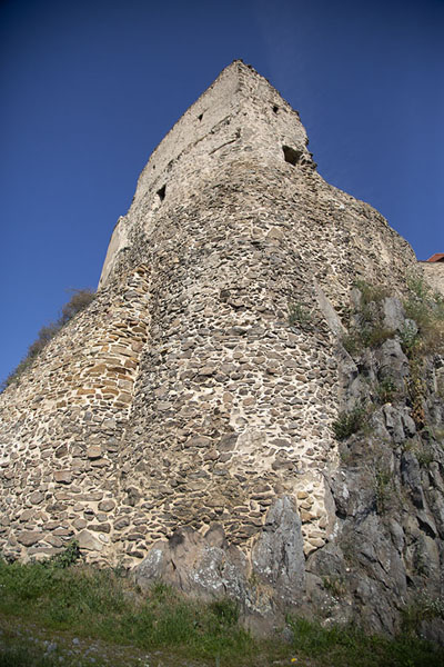 Looking up a rock with building on top | Alcázar de Rupea | Rumania