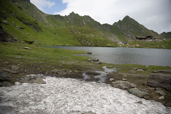 Bălea Lake with patch of snow and grass-covered mountains | Route du Transfăgărășan | Roumanie