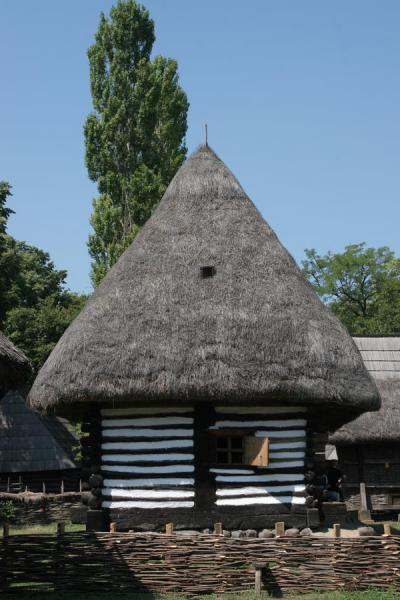 Hut-like house with black and white exterior in Village Museum | Musée du village Satului | Roumanie