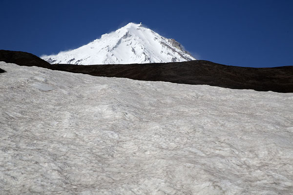 Picture of Koryaksky Volcano towering above the black volcanic landscape and snow field
