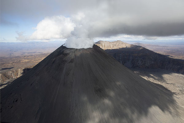 Karymsky volcano with smoke | Kamchatka from the air | Russia