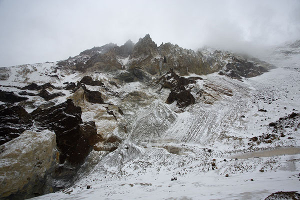 Entrance of the crater with snowy mountain slopes | Mutnovsky vulkaan | Rusland