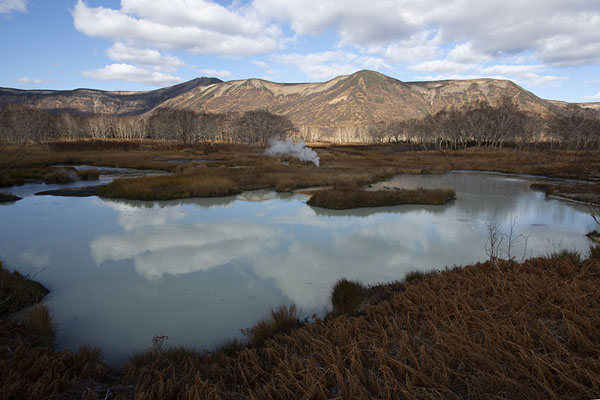 Photo de Mountains behind a pool in Uzon Caldera reflecting the clouds in the sky - Russie - Europe