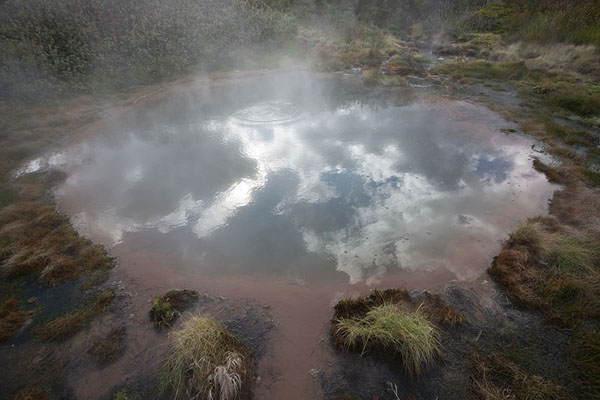 Foto van Sky with clouds reflected in pool of hot water in the Valley of GeysersVallei van de Geisers - Rusland