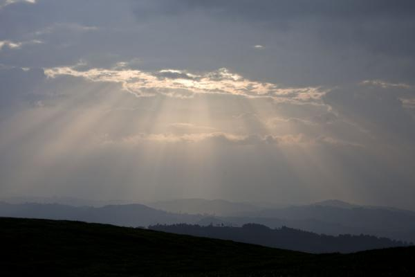 Sunlight shining through openings in the clouds over the landscape near Gisakura | Gisakura tea plantations | Rwanda