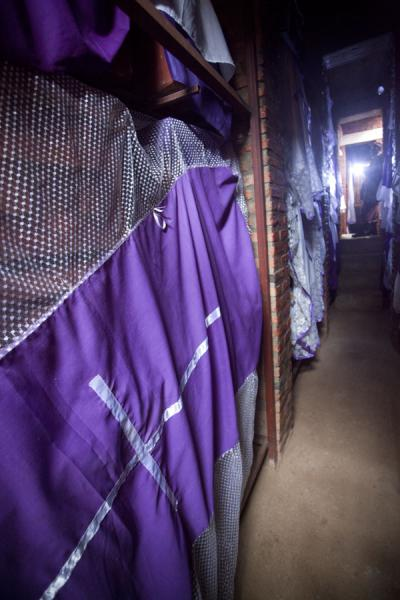 Purple curtains covering coffins and bones in one of the cellars | Nyamata Genocide Memorial | Rwanda