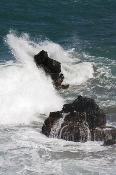 Foto van Wave enveloping a rock of black lavaBlack Rocks - St Kitts en Nevis