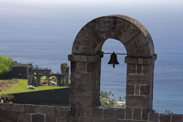 Picture of Brimstone Hill Fortress (Saint Kitts and Nevis): Bell of Fort George with sea and Artillery Offices in the background