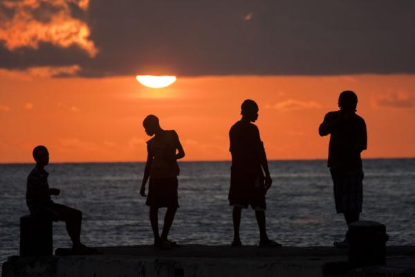 Foto van Santa Lucia (Sunset in Soufrière: men trying to catch fish from the main pier)