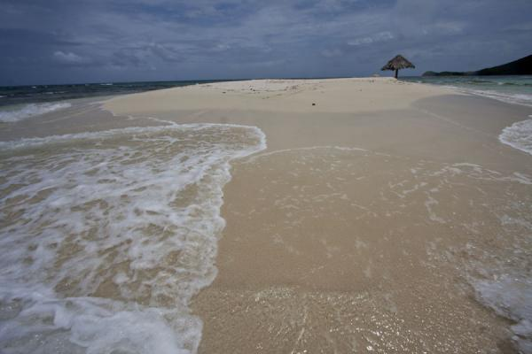 Waves on the sand in the foreground and lone parasol in the background | Morpion Islet | Saint Vincent and the Grenadines