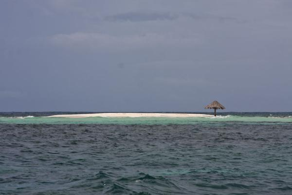 Picture of Morpion sand bank surrounded by green sea and topped with a lone parasol - Saint Vincent and the Grenadines - Americas