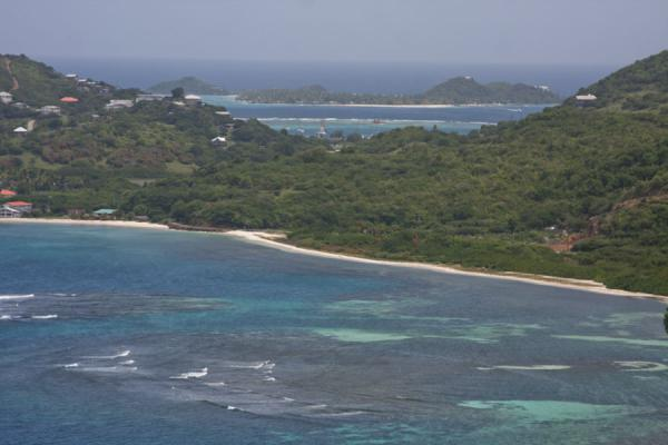 View over the coral-rich sea and beaches on the north side of Union Island, with Palm Island in the distance | Union  Island | Saint Vincent and the Grenadines