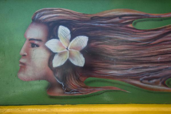 Close-up of the decoration on a bus with a girl and a frangipane flower in her hair | Busses de Samoa | Samoa