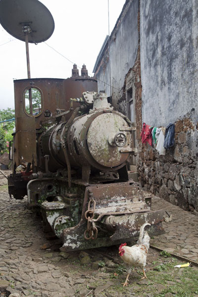 Picture of Sundy (São Tomé and Príncipe): Chicken walking past a rusty old locomotive in Sundy
