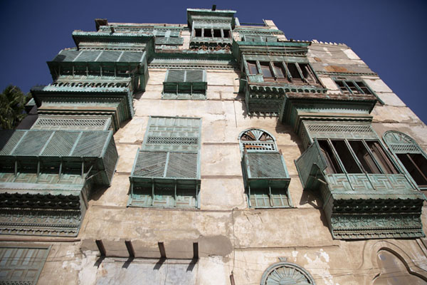 Looking up a tall building with wooden balconies in the late afternoon | Al Balad balconies | Saudi Arabia