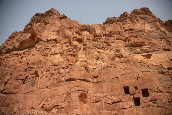 Looking up part of Jebel Khuraybah with some of the many tombs in the rock face | Dadan | Arabia Saudita