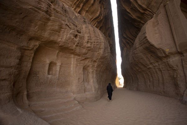 Woman walking the Siq, the natural passageway at Hegra | Hegra | Arabia Saudita