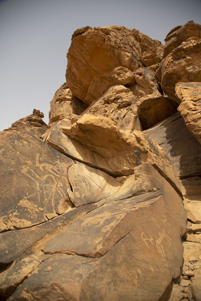 Looking up one of the rocky outcrops full of rock carvings | Petroglifi di Jubbah | Arabia Saudita