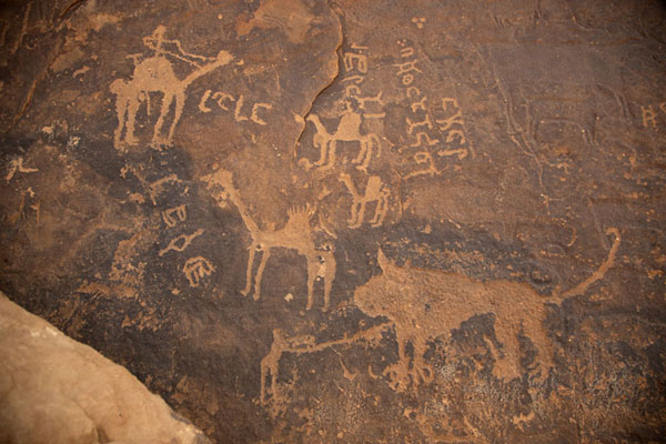Foto van Lion, camels and hunters depicted on a rock carvingJubbah - Saoedi Arabië