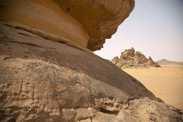 Foto van Top of one of the outcrops with carvings and another outcrop with carvings in the backgroundJubbah - Saoedi Arabië