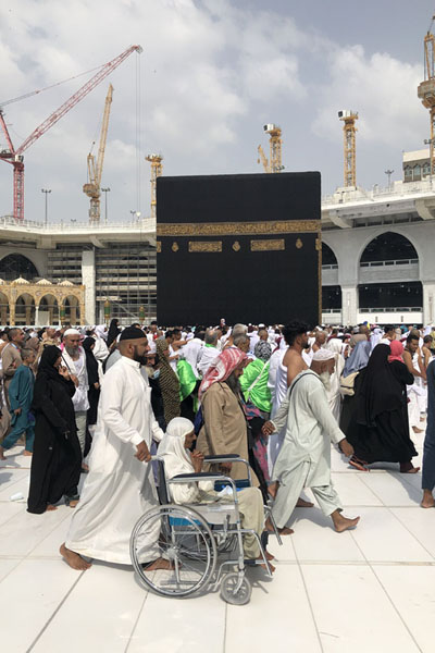 Pilgrim in a wheelchair being pushed around the Kaaba | Kaaba | Arabia Saudita
