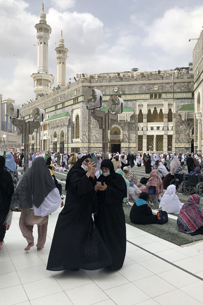 Two women taking a selfie at the square with the entrance of the Great Mosque in the background | Kaaba | Saoedi Arabië