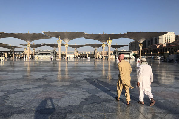 View of the enormous open plaza of the Prophet Mosque with umbrellas and worshippers | Medina mosques | Saudi Arabia