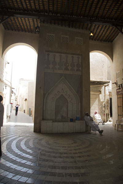 Picture of Qaisariah souq (Saudi Arabia): Man sitting at the well of Qaisariah souq