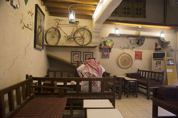 Picture of Qaisariah souq (Saudi Arabia): Saudi men sitting in quirky bar with bicycle on the wall in Qaisariah souq