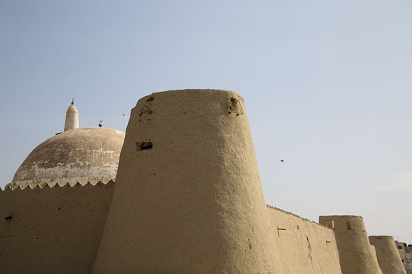 The adobe wall of Qasr Ibrahim with defensive towers and the dome of Quba mosque | Qasr Ibrahim | Saudi Arabia