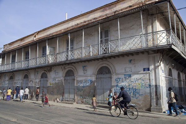 Picture of Man cycling past one of the typical buildings with balconies of Saint LouisSaint Louis - Senegal