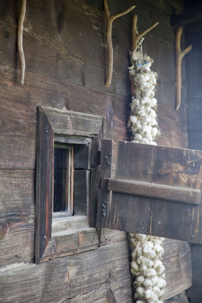 Exterior wall of cottage with string of garlic hanging down | Sirogojno village museum | Serbia